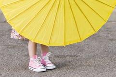 桃红色穿上鞋子黄色伞 免版税图库摄影