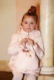 桃红色米黄外套的女孩有在她的现有量的袋子的坐 免版税库存图片