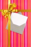 桃红色糖果条纹圣诞节或生日贺卡与金礼物丝带和弓和空插件与信封 库存图片
