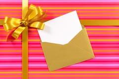 桃红色糖果条纹礼物,金丝带弓,空白的贺卡,信封,拷贝空间 免版税库存图片