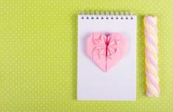 桃红色纸、开放笔记本有空白页的和棍子蛋白软糖华伦泰origami  免版税图库摄影