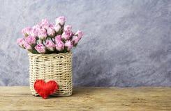 桃红色纸在老木头的帆布篮上升了 免版税库存照片