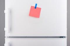 桃红色纸笔记附有与在白色冰箱的蓝色贴纸 免版税库存照片
