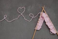 桃红色编织的羊毛和编织针与心脏形状从导线 深灰水泥背景 爱好和手工制造 免版税图库摄影