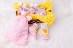 桃红色编织帽子和袜子礼物为一个新出生的女婴设置了 免版税库存照片