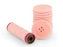桃红色缝合的被隔绝的按钮和螺纹 免版税库存图片