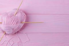 桃红色羊毛螺纹和木编织针在桃红色背景 顶视图,自由空间 库存图片