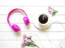 桃红色耳机和咖啡杯在木书桌桌上与桃红色花 音乐和生活方式概念 顶视图 库存图片