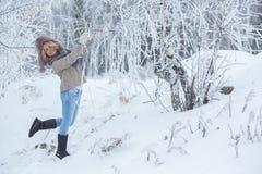 桃红色耳机的美丽的女孩在有雪的围巾 库存照片