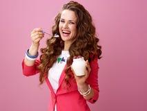 桃红色背景的微笑的妇女吃农厂有机酸奶的 库存照片