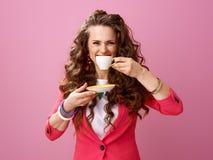 桃红色背景的微笑的时髦的妇女与咖啡 免版税库存图片