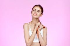 桃红色背景的美丽的妇女拿着一卷测量的磁带 库存图片