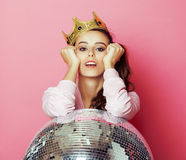 桃红色背景的年轻逗人喜爱的迪斯科女孩与迪斯科球和冠 库存图片