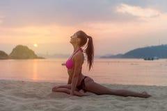 桃红色胸罩和黑内裤的少妇坐舒展她的腿的海滩在日落期间海上 健身女孩做 免版税库存图片