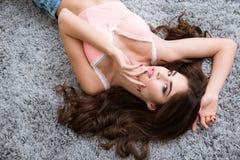 桃红色胸罩说谎和感人的面孔的诱人的年轻女性 免版税库存图片