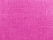 桃红色自然纺织品织地不很细背景  免版税库存照片