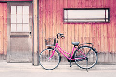 桃红色自行车和老木墙壁 库存图片