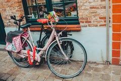 桃红色自行车和黑自行车在一条街道上在比利时 库存图片