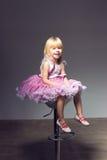 桃红色芭蕾舞短裙的,坐椅子的工作室女孩 库存图片