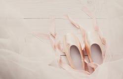 桃红色芭蕾pointe鞋子和芭蕾舞短裙在白色木背景 免版税库存图片