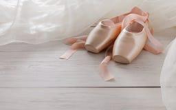 桃红色芭蕾pointe鞋子和芭蕾舞短裙在白色木背景 图库摄影