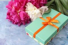 桃红色花和礼物盒在桌上 库存图片