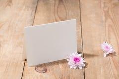 桃红色花和空的纸您的文本的在木背景 图库摄影