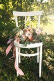 桃红色花和绿叶,在葡萄酒白色木椅子的谎言新娘花束  免版税库存照片
