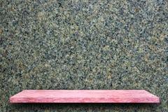 桃红色花岗岩石头桌空的上面在花岗岩墙壁backgr的 库存图片