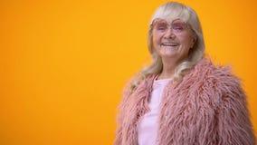 桃红色获得外套和圆的太阳镜的快乐的资深妇女乐趣,积极 股票视频