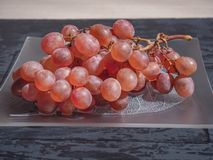 桃红色葡萄刷子在占领整个计划的一块装饰板材的 射击从端 免版税库存图片
