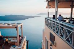 桃红色蓝色日落的看法在圣托里尼海岛上的到海、天空和海岛有松劲在一个咖啡馆的人的在 免版税图库摄影