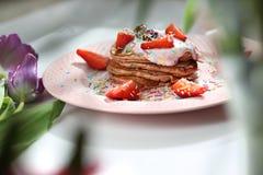 桃红色薄煎饼用草莓、酸奶干酪和五颜六色的糖洒 免版税库存照片