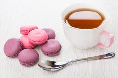 桃红色蛋白杏仁饼干堆,茶,在桌上的茶匙 库存图片