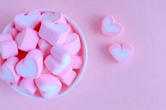桃红色蛋白软糖背景,在白色杯子, Val的心脏蛋白软糖 库存图片