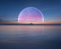 桃红色行星喜欢在海洋和山上的月亮 免版税图库摄影