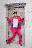 桃红色衣服和鞋子的年轻人站立与在墙壁 免版税库存照片