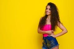 桃红色衬衣和蓝色的年轻和美丽的卷曲女孩短缺o 库存照片