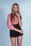 桃红色衬衣和黑短裤的美丽的女孩 免版税图库摄影