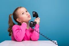 桃红色衬衣的可爱的矮小的逗人喜爱的女孩有猴子的和蓝色长裤举行空的海报和谈判电话 免版税库存图片
