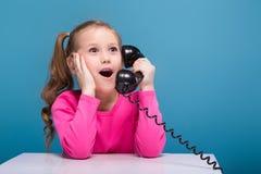 桃红色衬衣的可爱的矮小的逗人喜爱的女孩有猴子的和蓝色长裤举行空的海报和谈判电话 库存照片