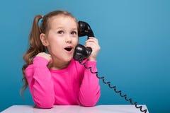 桃红色衬衣的可爱的矮小的逗人喜爱的女孩有猴子的和蓝色长裤举行空的海报和谈判电话 图库摄影