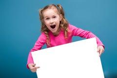 桃红色衬衣的可爱的矮小的逗人喜爱的女孩有猴子的和蓝色长裤拿着空的海报 库存图片