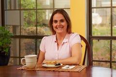 桃红色衬衣的妇女在桌上 免版税库存图片
