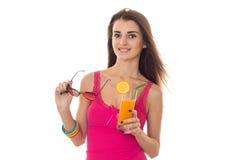 桃红色衬衣的年轻快乐的深色的女孩喝橙色鸡尾酒微笑在照相机的并且离开被隔绝的太阳镜  免版税图库摄影