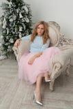 桃红色裙子和银鞋子的白肤金发的妇女在圣诞节t附近坐 库存照片