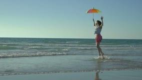 桃红色裙子的疯狂的滑稽的妇女有太阳镜的是跑和跳在海滩 假期来了 女孩愉快的上涨 股票视频