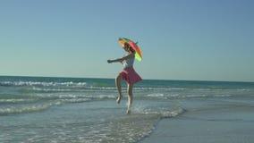 桃红色裙子的疯狂的滑稽的妇女有太阳镜的是跑和跳在海滩 假期来了 女孩愉快的上涨 影视素材