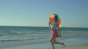 桃红色裙子的美丽的妇女有太阳镜的在海滩跳 愉快的女孩跳与彩虹伞 慢 股票录像