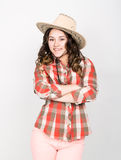 桃红色裤子、格子花呢上衣和牛仔帽的美丽的卷曲女孩 库存图片